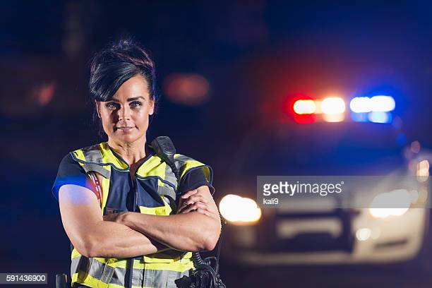 Policewoman in street at night, police car in background