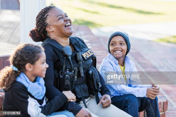 policewoman in the community, sitting with two children - officer stock pictures, royalty-free photos & images