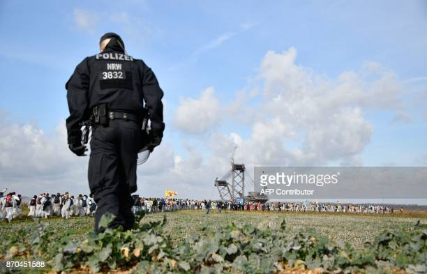 A policewoman looks on as environmentalist march close to the Hambach lignite open pit mine near Elsdorf western Germany on November 5 as they...