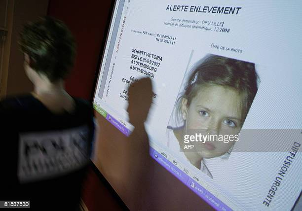"""Policewoman passes in front of a screen where an international simulated kidnapping alert is projected for the media to test the """"Plan Alerte..."""