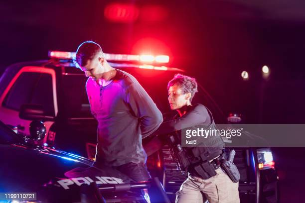 policewoman putting handcuffs on suspect - arrest stock pictures, royalty-free photos & images