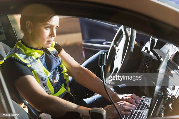 Policewoman sitting in patrol car using computer