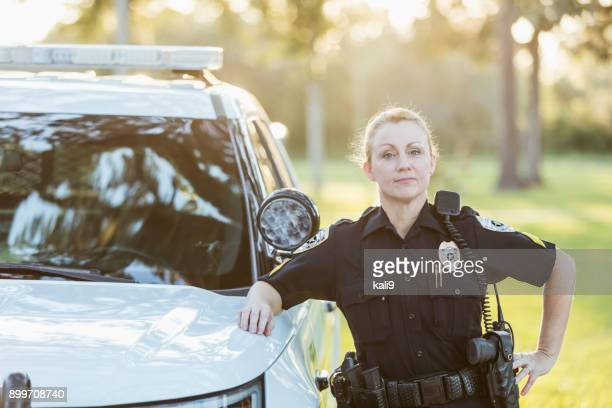 policewoman standing beside police squad car - police force stock pictures, royalty-free photos & images