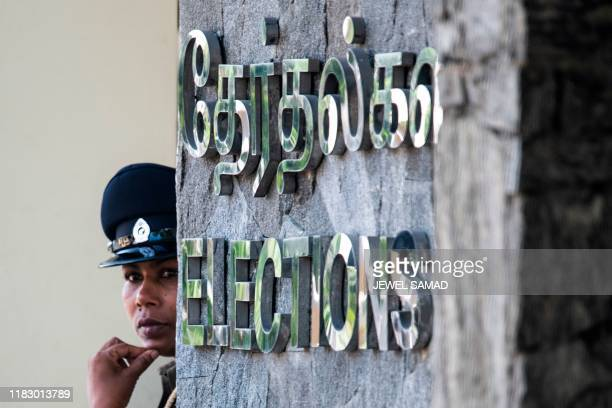 A policewoman stands guard at the election commission office in Colombo on November 17 before the arrival of Sri Lanka's Presidentelect Gotabaya...