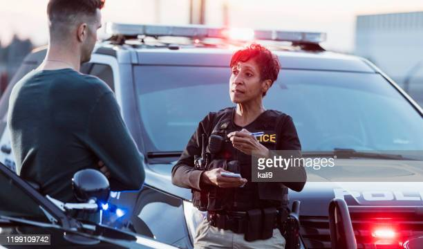 policewoman taking a statement from young man - police force stock pictures, royalty-free photos & images