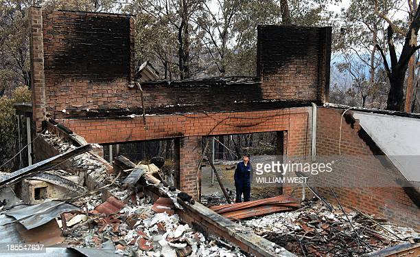 Policewoman Tegan Mobbs looks at the remains of her home in Yellow Rock in the Blue Mountains on October 22 after it was destroyed in a firestorm...