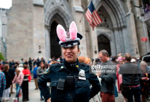 A policewoman wears bunny ears during the annual NYC Easter Parade and Bonnet Festival on 5th Avenue in Manhattan on April 21 2019 in New York City