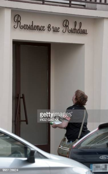 A policewoman works in front of a building after five people including one child were killed when a fire tore through an apartment in Pau...