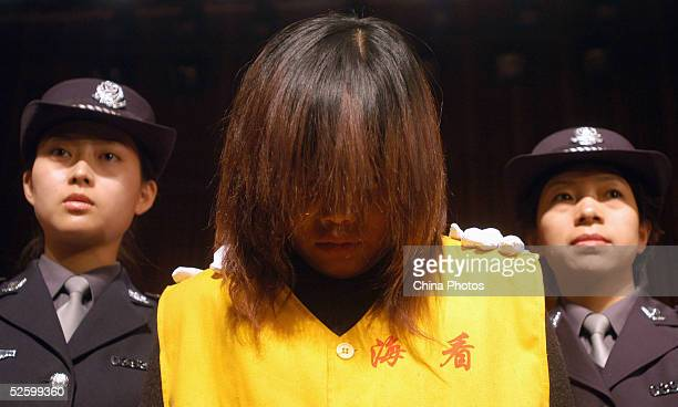 Policewomen parade a female suspect accused of sheltering prostitutes during a public sentencing April 7 2005 in Beijing China The local authorities...