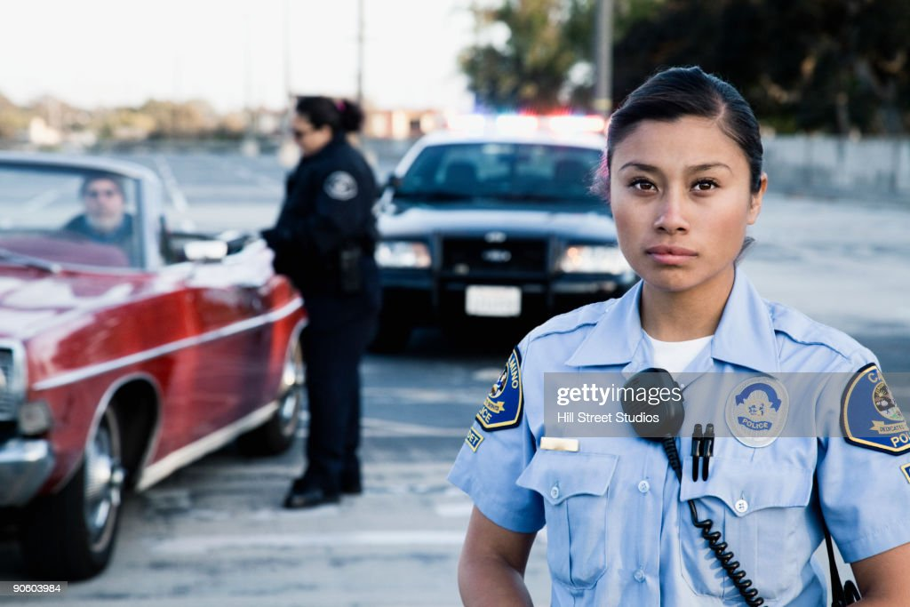 Policewomen pulling over man in convertible : Stock Photo