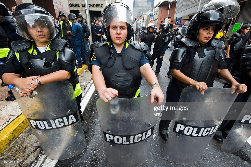 Policewomen stand guard during a protest of students and teachers in Caracas on May 27, 2010. The protest is in demand of a higher budget for educaction. AFP PHOTO / Miguel GUTIERREZ