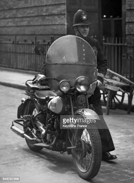 Policier poussant sa moto dans les rues de Londres RoyaumeUni en avril 1947