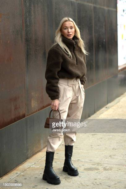 Polina Meshkova wears a Tularosa brown crop pullover, brown Revolve Grilfrnd pants, brown leather L' Intervalle bag and black L' Intervalle boots...