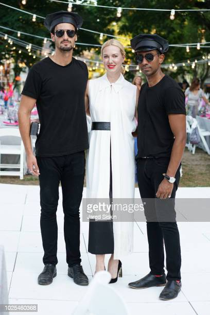 Polina Proshkina poses with waiters at SummerFest 2018 Honoring Peter Marino at Southampton Arts Center on August 30 2018 in Southampton New York