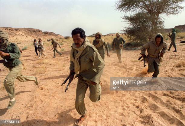 Polisario commandos scramble to take up positions near the front line with Morocco during an airraid drill 14 June 1988 in Polisariocontrolled...