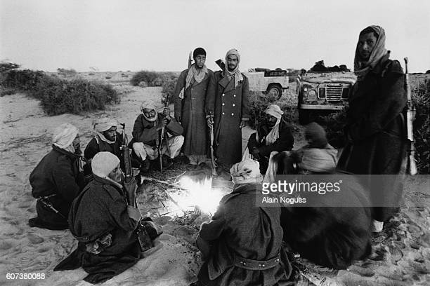 Polisario guerillas fighting for the liberation of the Saguia El Hamra and of the Rio de Oro gather around a campfire for tea at their bivouac in the...