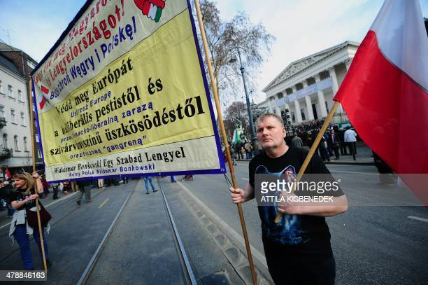 """Polish activists hold a banner reading """" 'God saves Hungary and Poland! Defend Europe against the plague of the liberalism and the rainbow colored..."""