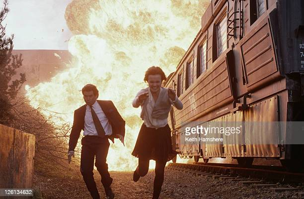 Polish actress Izabella Scorupco and Irish actor Pierce Brosnan flee from an exploding train in a scene from the James Bond film 'GoldenEye' 1995
