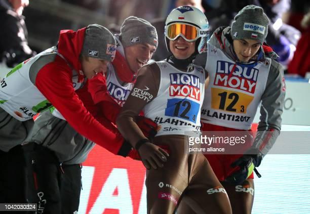 Polish athletes Dawid Kubacki Piotr Zyla Kamil Stoch and Maciej Kot celebrate their gold in the men's ski jumping team event at the Nordic Ski World...