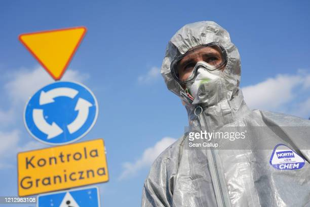 Polish border guard dressed in a protective suit, mask and goggles waits to measure the body temperature people arriving to enter Poland as an...