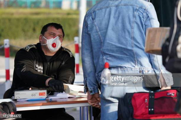 Polish border guard wearing a protective face mask against the coronavirus speaks with people arriving to enter Poland at the Polish/German border at...