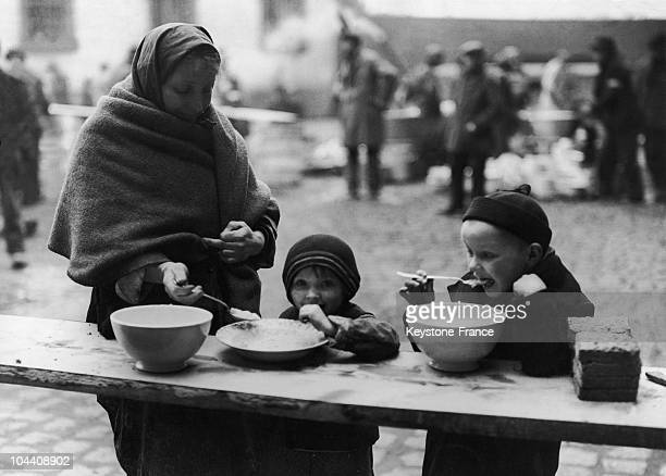 Polish children at the dispersal point eating with their mother on March 1945 3600 displaced persons Russians Poles French Belgians Spaniars...