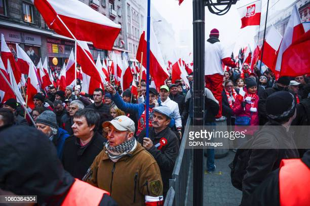 Polish citizens holding Polish flags during the official march organized by the Polish government at Rondo Dmowskiego. Days before the Independence...