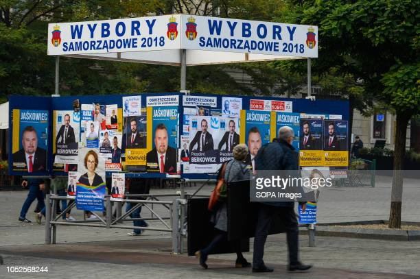 Polish citizens stand while looking at a sign board with information about the local elections at the Main Square On October 21 2018 Polish citizens...