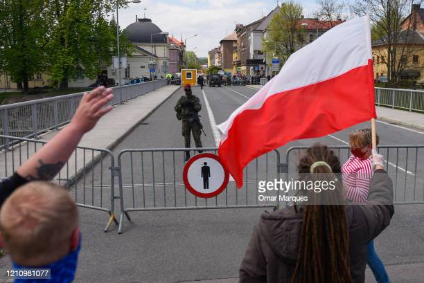 Polish citizens wear protective masks as they hold a Polish flag and wave to Poles on the Czech side of the border during a protest against the...