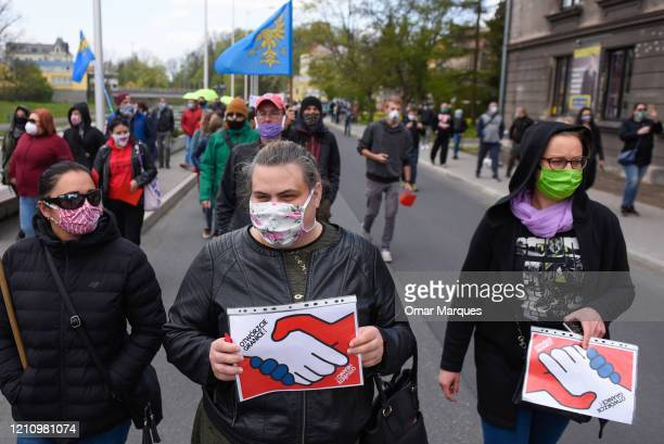 Polish citizens wear protective masks as they hold banners during a protest against the ongoing closure of the Polish Czech border which was...
