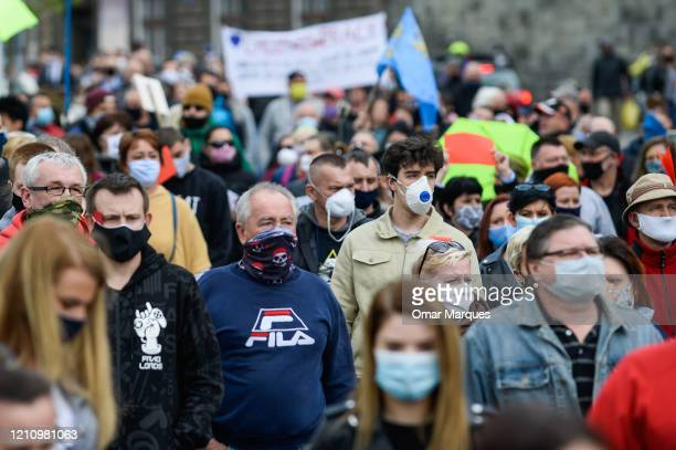 Polish citizens wear protective masks as they hold red cards, banners and shout slogans during a protest against the ongoing closure of the Polish...