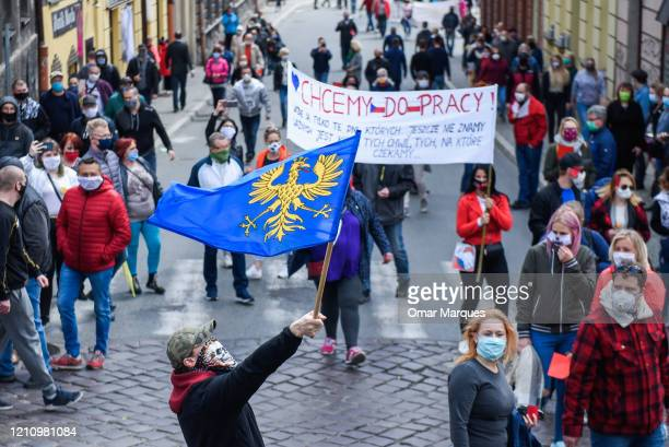 Polish citizens wear protective masks as they protest against the ongoing closure of the Polish Czech border which was implemented by the Polish...