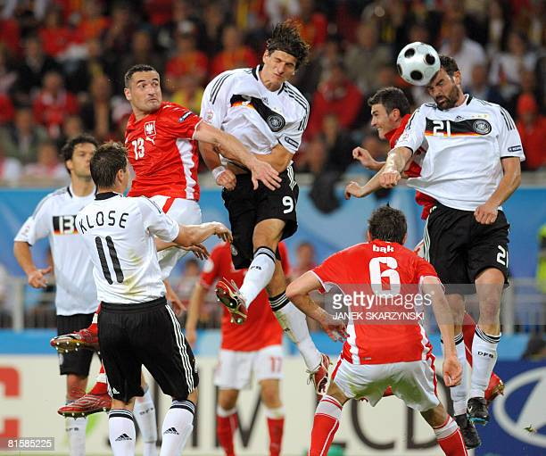 Polish defender Marcin Wasilewski German forward Mario Gomez and German defender Christoph Metzelder jump for the ball during their Euro 2008...