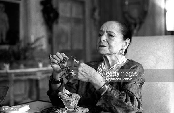 'Polish entrepreneur and founder of the cosmetic company bearing her same name Helena Rubinstein stripping the petals off a flowers New York April...
