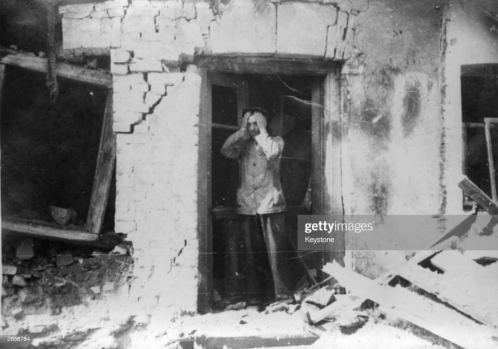 A Polish farmer at the door of his home, head in his hands in despair, surveys the wreckage caused by a German air raid during the invasion of Poland.