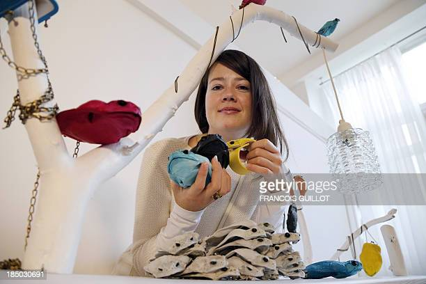 Polish fashion designer Monika Jarosz poses with her products made with Australian cane toads on October 9 2013 in Paris AFP PHOTO / FRANCOIS GUILLOT