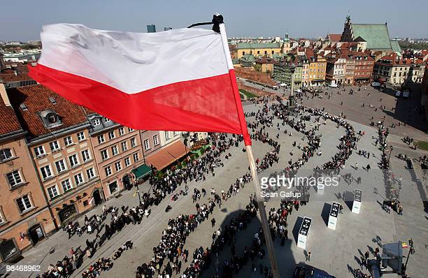 Polish flag adorned with a black strip flies high above mourners waiting in a snaking line to pay their last respects at the coffins of late Polish...