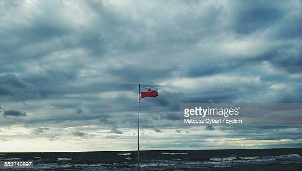 Polish Flag Waving At Beach Against Cloudy Sky