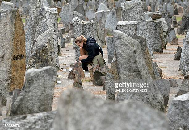 A Polish girl scout lights a candle in front of the monument of Treblinka World War IIera Nazi death camp on October 2 2013 in Treblinka Around 600...