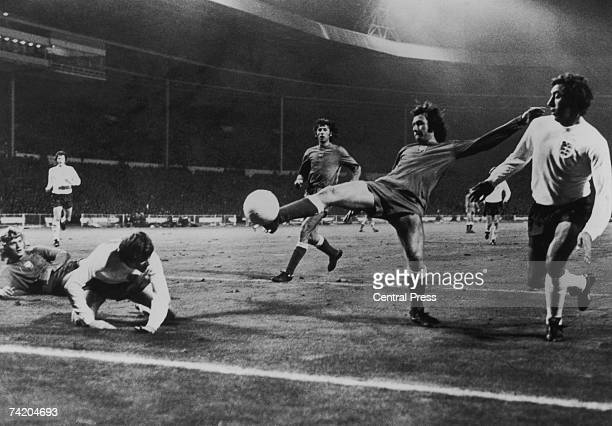 Polish goalkeeper Jan Tomaszewski watches from the ground as a Polish defender clears the ball during an attack by Alan Clarke and Martin Chivers...