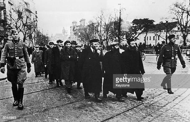 Polish Jews being escorted through a street in Warsaw to a concentration camp by members of the Gestapo during World War II