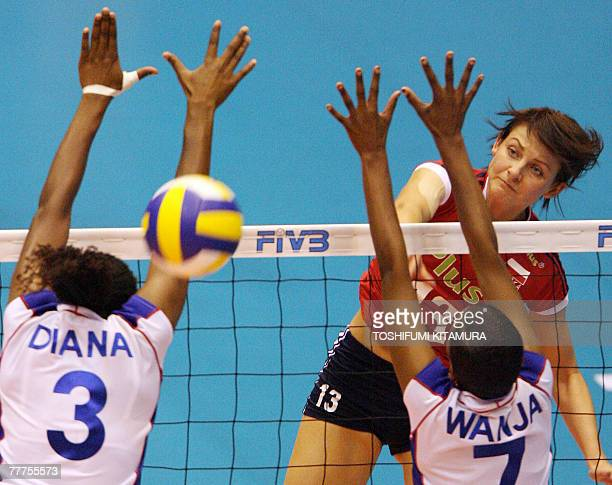 Polish Milena Rosner spikes the ball past Kenya's Diana Khisa and Janet Wanja during their FIVB Women's World Cup second round match in Sendai 07...