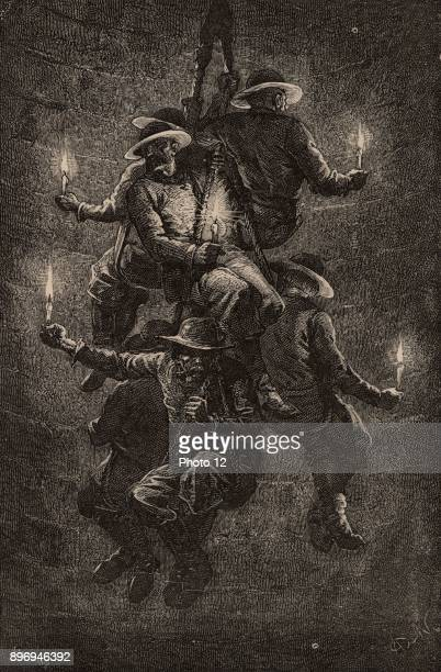 Polish miners at Wielleczka salt mine descending the shaft in a group of six each sitting in a loop of rope with all six loops attached to a single...
