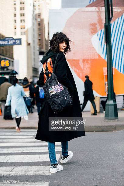Polish model Ewa Wladymiruk wears a black MISBHV 'Heads' graphic oversize wool coat with distressed finishing a Star Wars backpack and blue Adidas...