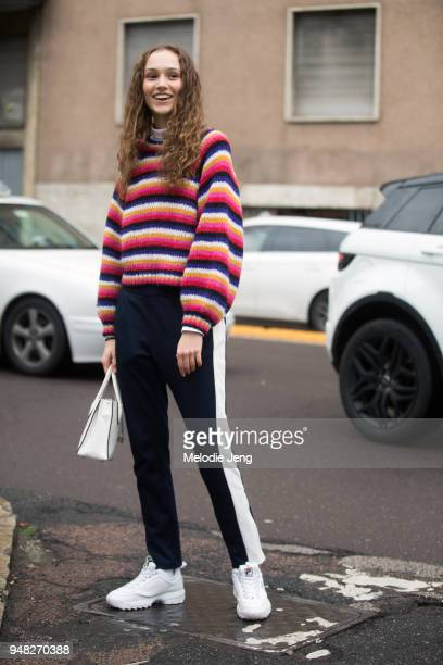Polish model Michelle Gutknecht wears a white pink and blue striped sweater blue runner pants with a white stripe a white purse and white chunky Fila...