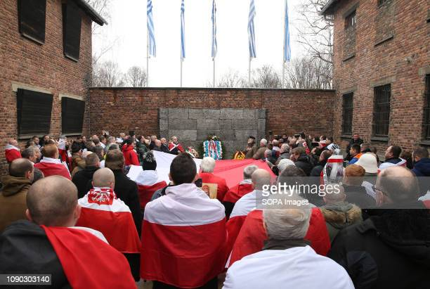Polish patriots with national flags are seen on the death wall at the former Nazi-German concentration and extermination camp Auschwitz during the...
