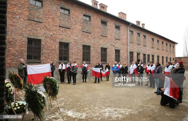 Polish patriots with national flags are seen on the death wall at the former NaziGerman concentration and extermination camp Auschwitz during the...