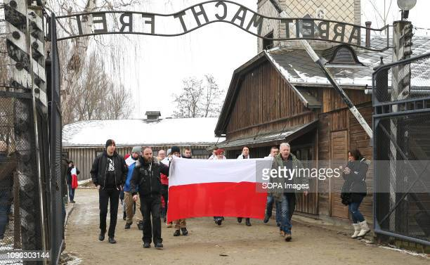 Polish patriots with national flags are seen walking through the famous main gate at the former NaziGerman concentration and extermination camp...