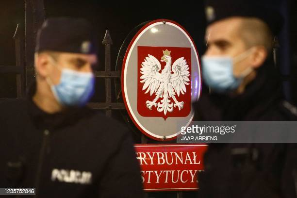 Polish policemen patrol in front of the entrance to the Constitutional Court with the coat of arms of Poland, in Warsaw on October 7 as the court...