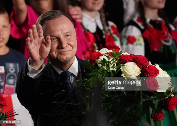 Polish President and member of the right-wing Law and Justice party Andrzej Duda gestures to supporters following initial results in the Polish...